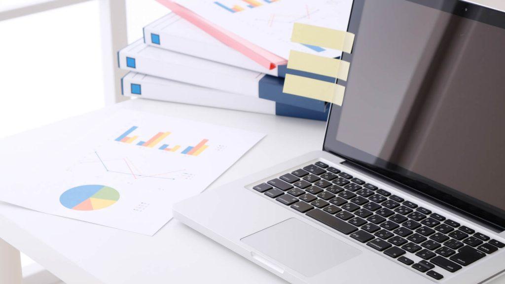 デスク上の資料とノートパソコン